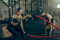 Woman with battle ropes exercise in the fitness gym. - PhotoDune Item for Sale
