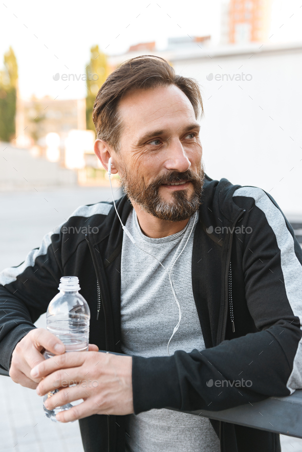 Handsome strong mature sportsman holding bottle with water. - Stock Photo - Images