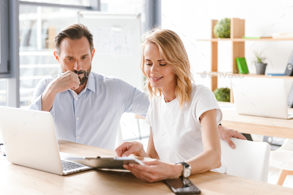 Couple of young colleagues working together - Stock Photo - Images