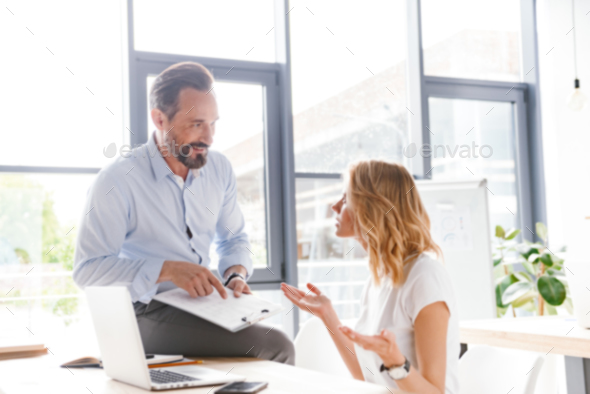 Couple of colleagues discussing work while sitting - Stock Photo - Images