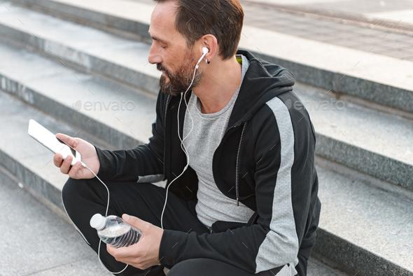 Focused sportsman in earphones - Stock Photo - Images