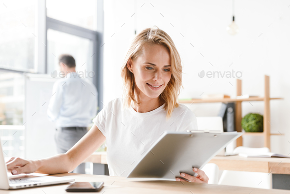 Smiling woman manager working on laptop computer - Stock Photo - Images