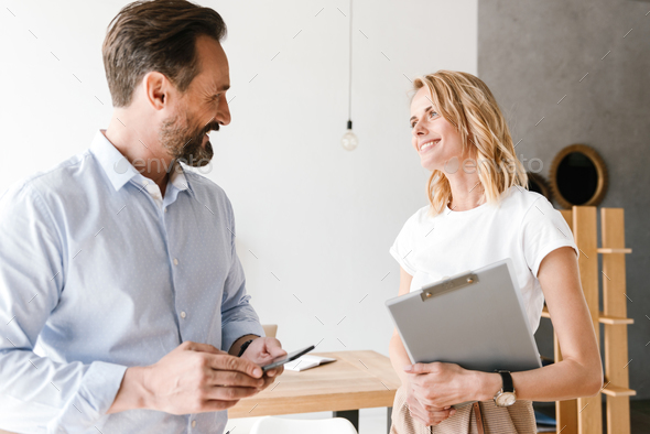Couple of happy colleagues talking - Stock Photo - Images
