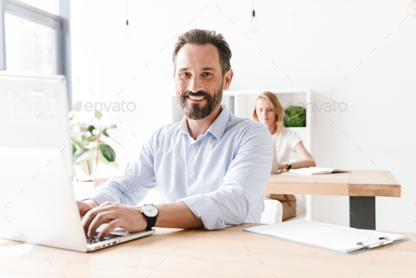 Happy man manager working on laptop computer - Stock Photo - Images