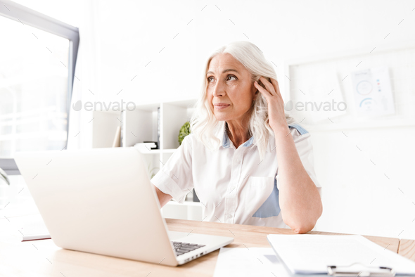 Concentrated mature woman sitting indoors working - Stock Photo - Images
