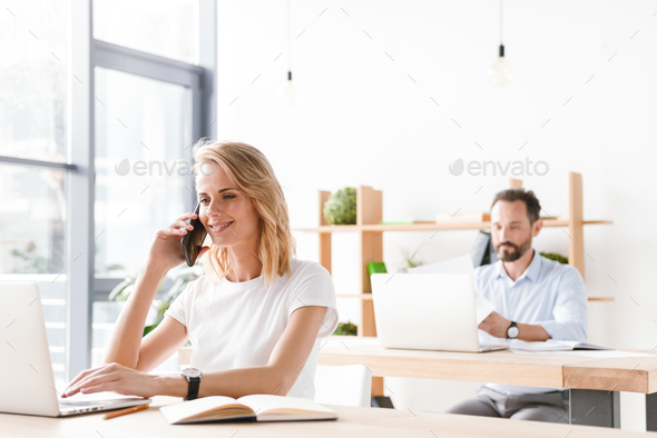 Smiling woman manager working with laptop computer - Stock Photo - Images