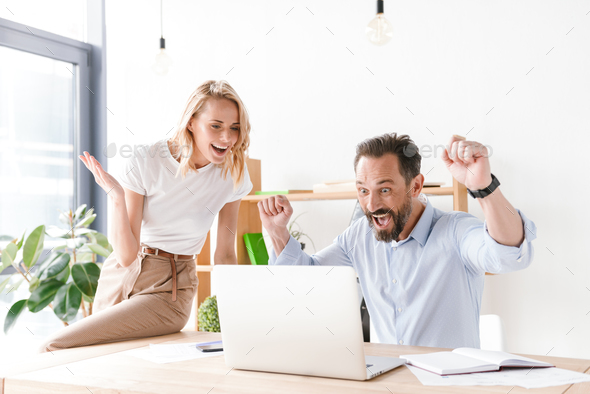Couple of happy colleagues celebrating success - Stock Photo - Images
