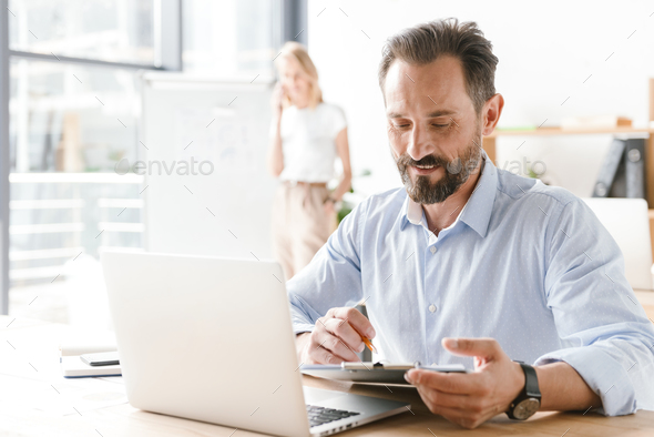 Confident man manager working on laptop computer - Stock Photo - Images