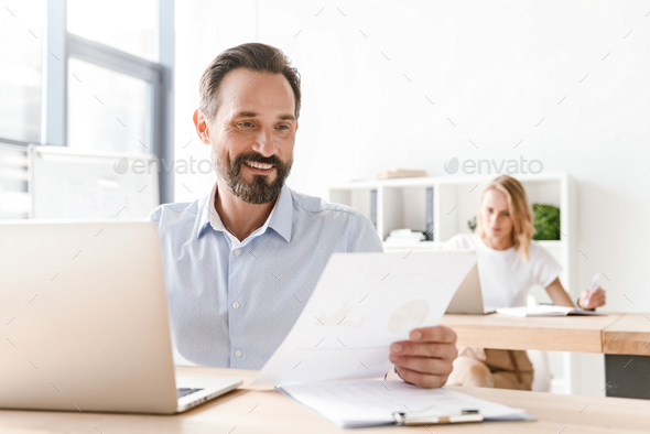 Smiling man manager working on laptop computer - Stock Photo - Images