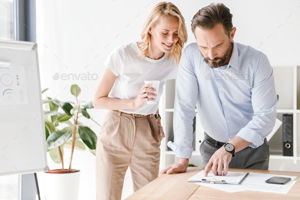 Couple of smiling colleagues discussing work - Stock Photo - Images