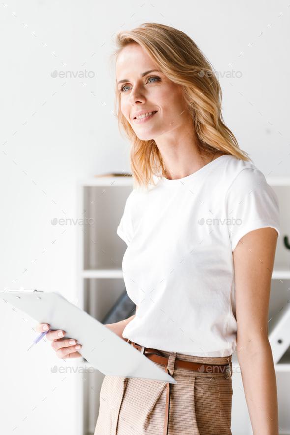 Smiling businesswoman holding folder - Stock Photo - Images