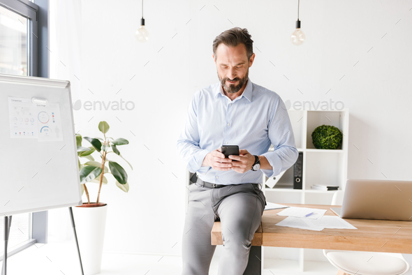 Smiling businessman using mobile phone - Stock Photo - Images