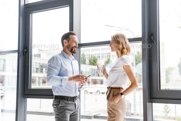 Couple of smiling colleagues talking - Stock Photo - Images
