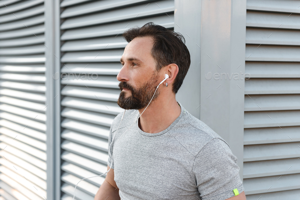 Handsome strong mature sportsman listening music with earphones. - Stock Photo - Images