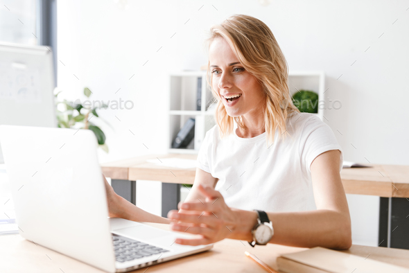 Excited businesswoman working on laptop computer - Stock Photo - Images