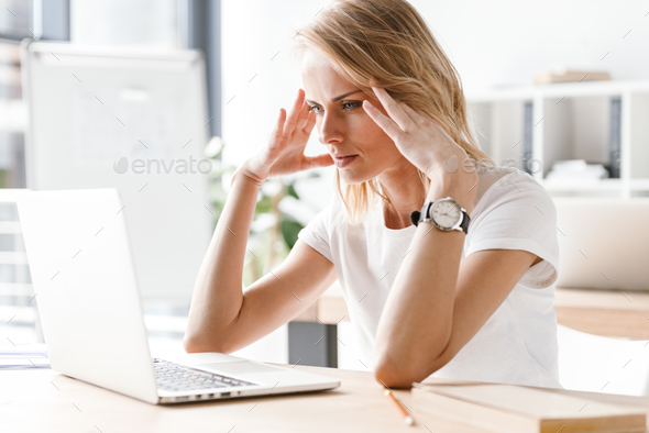 Tired businesswoman working on laptop computer - Stock Photo - Images