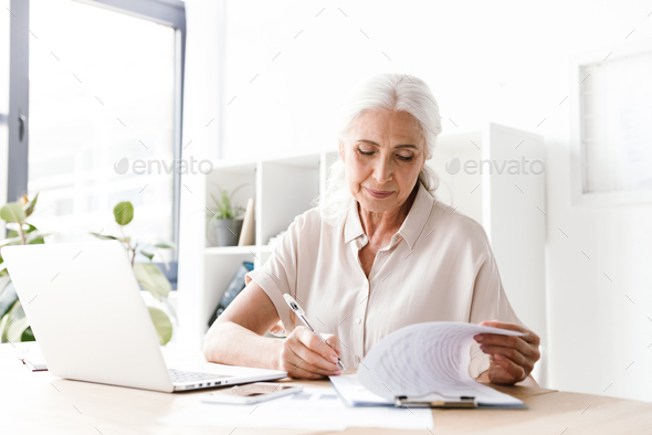 Mature happy woman writing notes. - Stock Photo - Images