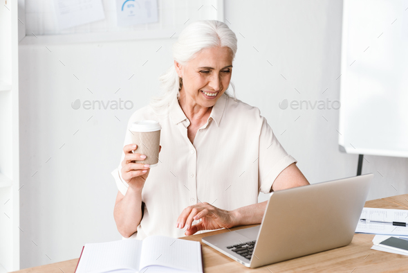 Smiling mature business woman working on laptop - Stock Photo - Images