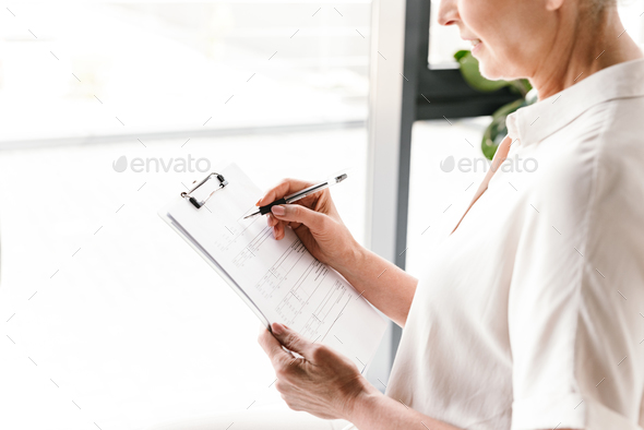 Close up of mature business woman taking notes - Stock Photo - Images