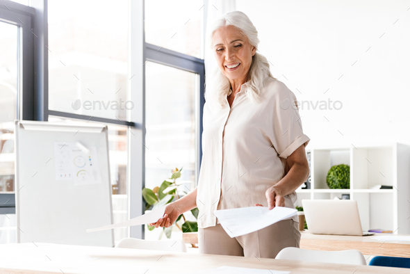 Happy mature business woman analyzing documents - Stock Photo - Images