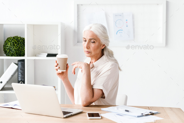 Confident mature business woman working on laptop - Stock Photo - Images