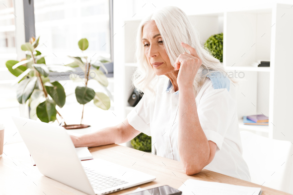 Concentrated mature woman sitting indoors in office - Stock Photo - Images