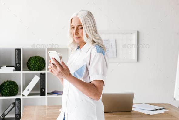 Mature happy woman drinking coffee using mobile phone. - Stock Photo - Images