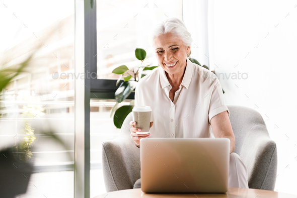 Happy mature business woman working on laptop computer - Stock Photo - Images