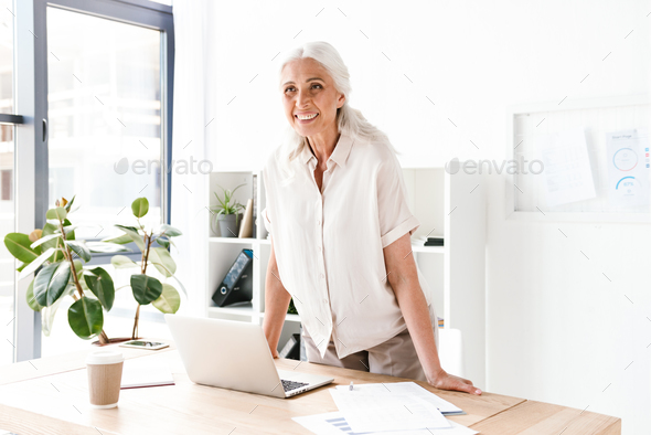 Happy mature business woman leaning on desk - Stock Photo - Images