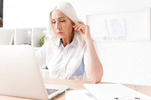Serious mature woman sitting indoors in office working - Stock Photo - Images