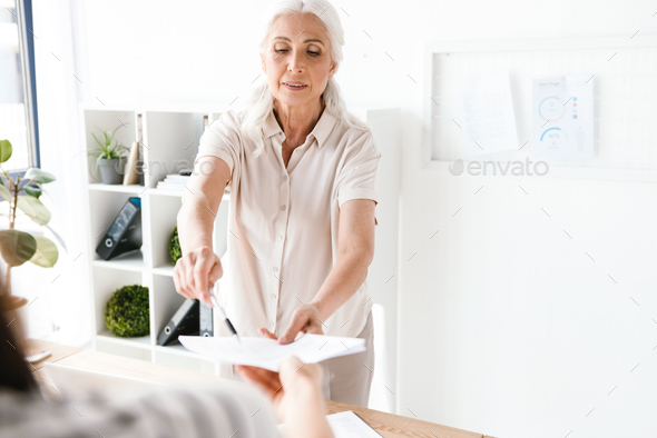 Confident mature busienss woman giving documents - Stock Photo - Images