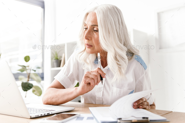 Mature concentrated woman writing notes. - Stock Photo - Images
