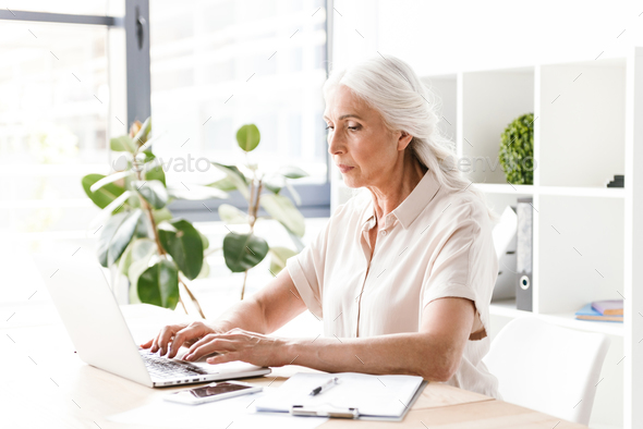Woman sitting indoors in office working with laptop computer. - Stock Photo - Images