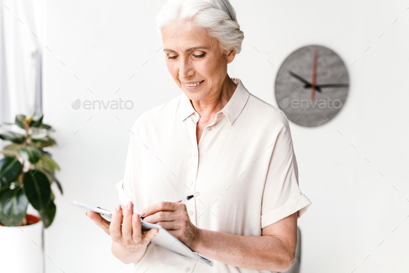 Smiling mature business woman taking notes - Stock Photo - Images