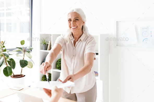 Happy mature busienss woman giving documents - Stock Photo - Images