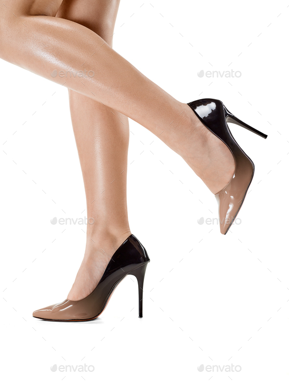 Tanned female legs in high heels isolated on white background. - Stock Photo - Images