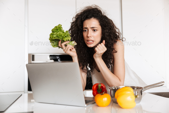 Photo of concentrated curly woman 20s holding green salat and re - Stock Photo - Images