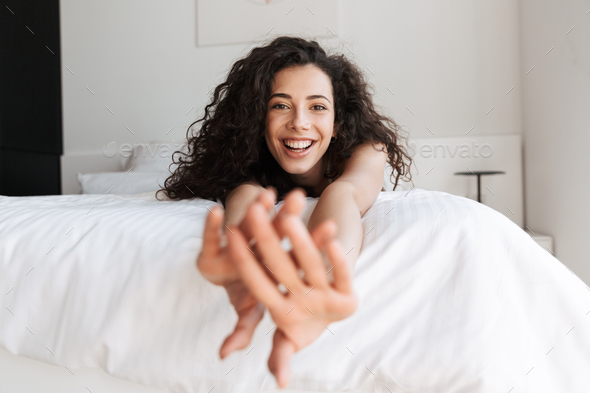 Portrait of prettyy european woman with long curly hair lying in - Stock Photo - Images