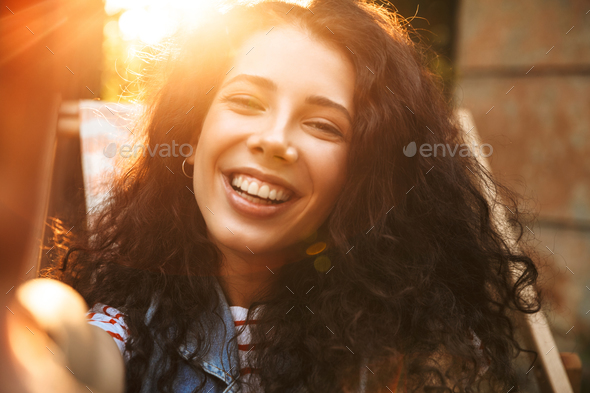 Happy young beautiful curly woman outdoors - Stock Photo - Images