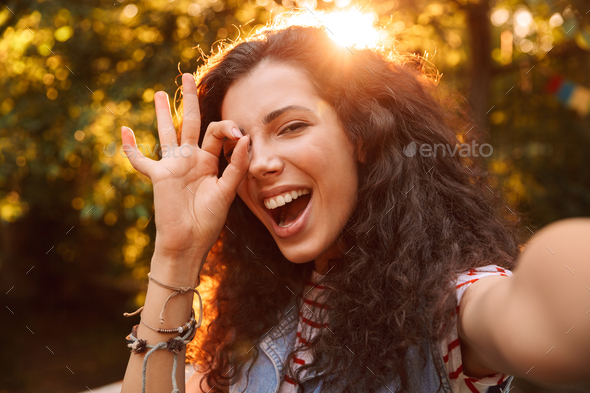Caucasian curly girl 18-20 looking at camera, through ok sign wh - Stock Photo - Images