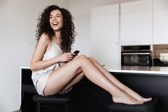 Photo of joyful cute woman 20s with curly hair looking aside, wh - Stock Photo - Images