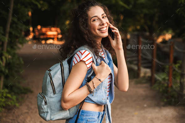 Image of young brunette student 18-20 wearing backpack, smiling Stock Photo by vadymvdrobot
