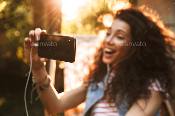 Cute young beautiful curly woman listening music with earphones. - Stock Photo - Images