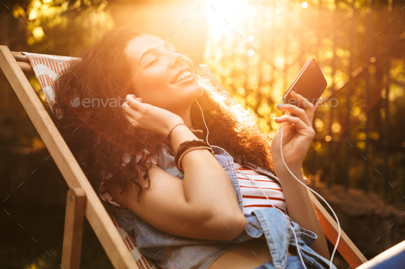 Cute young beautiful curly woman holding mobile phone listening music with earphones. - Stock Photo - Images