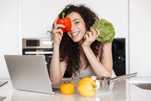 Photo of cheerful woman vegetables lover holding green salat and - Stock Photo - Images