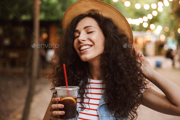 Photo of delighted cute woman 18-20 wearing summer straw hat dri - Stock Photo - Images