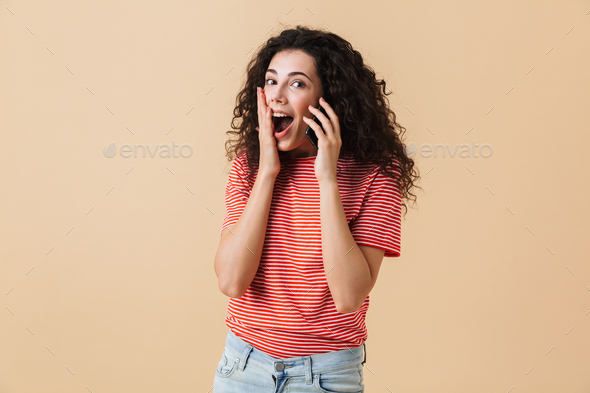 Portrait of an excited young girl with curly hair - Stock Photo - Images