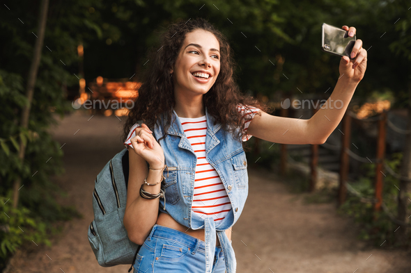 Photo of brunette pretty woman 18-20 with backpack, laughing and - Stock Photo - Images