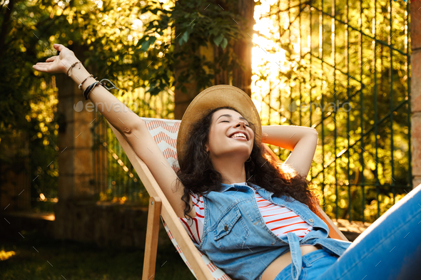 Beautiful cheerful curly woman outdoors in park have a rest - Stock Photo - Images