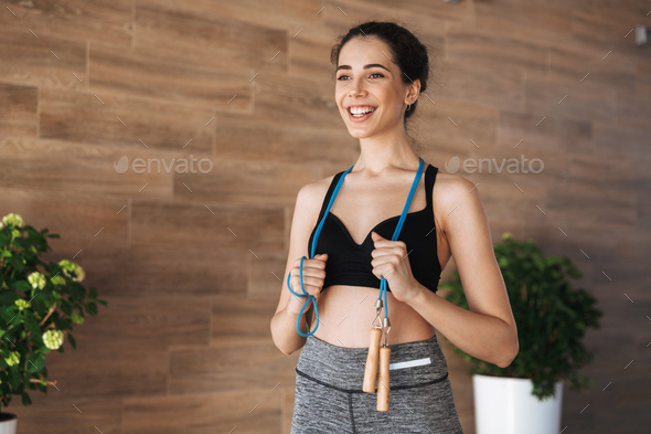 Happy young sportswoman holding skipping rope - Stock Photo - Images